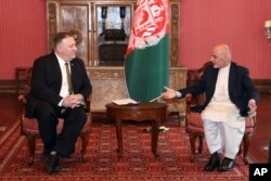 U.S. Secretary of State Mike Pompeo, left, meets with Afghan President Ashraf Ghani, at the Presidential Palace in Kabul, Afghanistan, March 23, 2020.