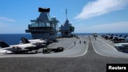 """资料照片:""""伊丽莎白女王""""号航母及舰载F-35B战机在葡萄牙附近海域参加北约演习。(2021年5月21日)"""
