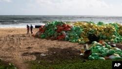 Ljudi hodaju pored hrpe plastike koju je okean izbacio na obalu nakon požara na kontejnerskom teretnjaku MV X-Press Pearl u Kapungodi, u predgrađu Kolumba, Šri Lanka, 11. juna 2021.