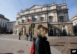 A woman wearing a protective mask walks past La Scala Opera house in Milan, Italy, Feb. 24, 2020.