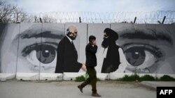 مردی از مقابل تصویر زلمای خلیل زاد، نماینده آمریکا در مذاکرات صلح افغانستان، و ملا عبدالغنی برادر، از بنیانگذاران طالبان، در کابل عبور می کند. ۵ آوریل ۲۰۲۰