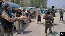 A Pakistani paramilitary soldier, left, and Taliban fighters stand guard on their respective sides, at a border crossing point between Pakistan and Afghanistan, in Torkham, in Khyber district, Pakistan, Sept. 5, 2021.