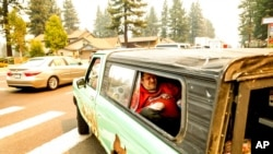 A Tahoe resident lies in a pick-up truck while evacuating as the Caldor Fire approaches South Lake Tahoe, Calif., Aug. 30, 2021.