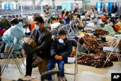 Evacuees from Afghanistan wait with other evacuees to fly to the United States or an other safe location in a makeshift departure gate inside a hangar at the U.S. airbase in Ramstein, Germany, Sept. 1, 2021.