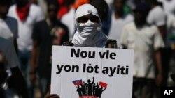"""Yon manifestan ki kenbe yon pankat ki ekri, """"Nou vle yon lòt Ayiti."""" Port-au-Prince, Haiti, Oct. 13, 2019."""