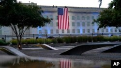 An American flag is unfurled at the Pentagon in Washington, Sept. 11, 2021, at sunrise on the morning of the 20th anniversary of the terrorist attacks.