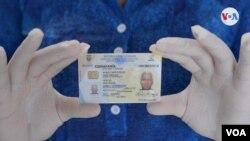 Sharon Ayala muestra la cédula de identidad de su padre que murió por la COVID-19 y a quien no pudo darle sepultura.