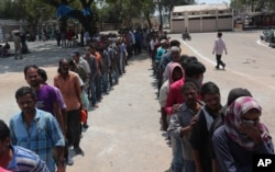 FILE - Impoverished Indians stand in queues to receive free food in Hyderabad, India, March 27, 2020.