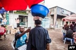 FILE - A health worker checks a man's temperature in Goma, July 31, 2019.
