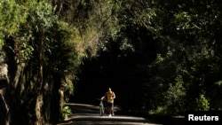 FILE - A man walks with his bicycle through the Tijuca Forest in Rio de Janeiro, Brazil, July 29, 2012.