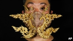 Edmond Kok, a Hong Kong theater costume designer and actor, wearing a face mask inspired by the decoration of Thai temple to Kok's face in Hong Kong Thursday, Aug. 6, 2020. With little theater work…