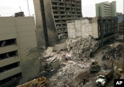 FILE - The United States Embassy, left, is pictured with blasted ruins next to it in downtown Nairobi, Kenya, Aug. 8, 1998, the day after terrorist bombings in Kenya and Dar es Salaam, Tanzania.