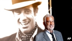 FILE - French actor Jean-Paul Belmondo poses for photographers as he arrives at the opening ceremony of the 5th edition of the Lumiere Festival, in Lyon, central France, Oct. 14, 2013.
