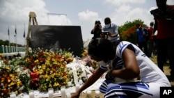 Une femme allume une bougie à un mémorial à l'extérieur du palais présidentiel à la mémoire du président assassiné Jovenel Moise, à Port-au-Prince, Haïti, le 14 juillet 2021.