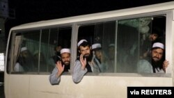FILE - Newly freed Taliban prisoners are seen inside a bus at Bagram prison, north of Kabul, Afghanistan, April 11, 2020.