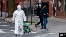 Žena u zaštitnom odelu izlazi iz prodavnice u Kvinsu, u Njujorku (Foto: AFP/Johannes Eisele)