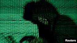 Seorang pria memegang laptop untuk berusaha meretas kode-koder siber dalam gambar ilustrasi yang diambil pada 13 Mei 2017. (Foto: Reuters)