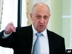 FILE - Yevgeny Prigozhin gestures during a meeting outside St. Petersburg, Russia, Aug. 9, 2016.