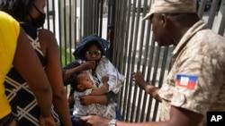 Pripadnik policije Haitija traži od žene da se udalji od ograde Ambasade SAD u Port-Prensu, Haiti, 9. jula 2021.