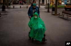 Un hombre que usa una máscara facial y una capa para cubrir la lluvia es trasladado en una silla de ruedas a lo largo de un bulevar en Barcelona, España, el miércoles 9 de septiembre de 2020.