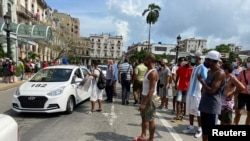 People gather near police cars during protests against and in support of the government, amidst the coronavirus disease (COVID-19) outbreak, outside the Capitol building, in Havana, Cuba, July 11, 2021.