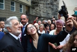 FILE - Placido Domingo poses for selfies at the Festspielhaus opera house after he performed Luisa Miller by Giuseppe Verdi in Salzburg, Austria, Aug. 25, 2019.