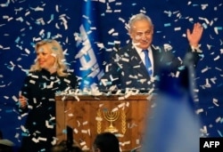 Israeli Prime Minister Benjamin Netanyahu and his wife, Sara, address supporters as confetti falls upon them at the Likud party campaign headquarters in Tel Aviv, March 3, 2020.