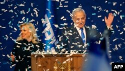 Israeli Prime Minister Benjamin Netanyahu and his wife, Sara, address supporters as confetti falls upon them at the Likud party campaign headquarters in the coastal city of Tel Aviv, after polls officially closed.