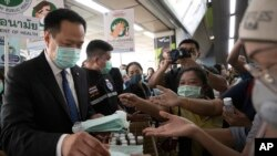 Thailand's Public Health Minister Anutin Charnvirakul, left, distributes masks to commuters during a campaign for wearing masks and washing hands at the skytrain station in Bangkok, Thailand, Friday, Feb. 7, 2020. The coronavirus outbreak in China…
