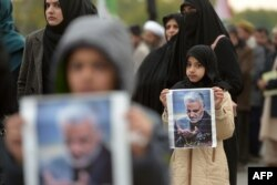 Protesters carry posters with the image of top Iranian commander Qassem Soleimani, who was killed in a U.S. airstrike in Iraq, during a demonstration in Islamabad.
