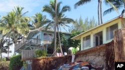 FILE - Sandbags are piled up in front of properties damaged by severe beach erosion in the Rocky Point neighborhood of Oahu's North Shore in Haleiwa, Hawaii, Dec. 31, 2013.
