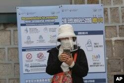 Женщина в медицинской маске на улице в Сеуле, Южная Корея