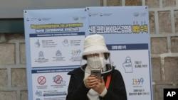 韩国首尔市一位戴着口罩的女士正在查看手机(2020年3月21日)