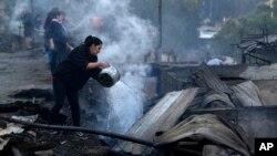 Seorang warga berusaha memadamkan api di antara reruntuhan rumah yang terbakar di Valparaiso, Chili Rabu (25/12).