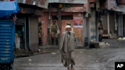 Seorang pria Kashmir berjalan di tengah jalanan yang sepi, di Srinagar, kawasan Kashmir yang dikuasai oleh India, diawasi oleh para penjaga keamanan, 14 Agustus 2019.