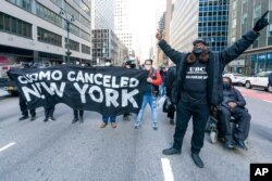 FILE - Activists with VOCAL-NY block traffic outside New York Gov. Andrew Cuomo's office, demanding his resignation, in New York, March 10, 2021.