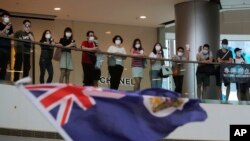 """Waandamanaji wakiimba """"Glory to Hong Kong"""" and na kupeperusha bendera katika eneo la biashara mjini Hongo Kong, Ijumaa, Mei 29, 2020."""