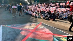 FILE - A large image that has an X mark on the face of Commander in chief Senior Gen. Min Aung Hlaing, also chairman of the State Administrative Council, lies on a road as anti-coup protesters gather outside the Hledan Centre in Yangon, Myanmar, Feb. 14, 2021.