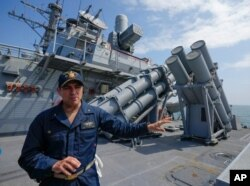 FILE - John D. John, commanding officer of guided-missile destroyer USS Ross, speaks to reporters during Sea Breeze 2021 maneuvers, in the Black Sea, July 7, 2021.