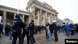 Demonstrators are detained by police officers during a protest against the government's coronavirus disease (COVID-19) restrictions, next to the Brandenburger Gate in Berlin, Nov. 18, 2020.
