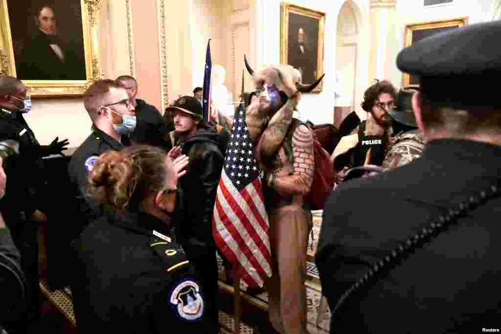 La policía confronta a partidarios del presidente Donald Trump mientras se manifiestan en el segundo piso del Capitolio de los EE. UU.