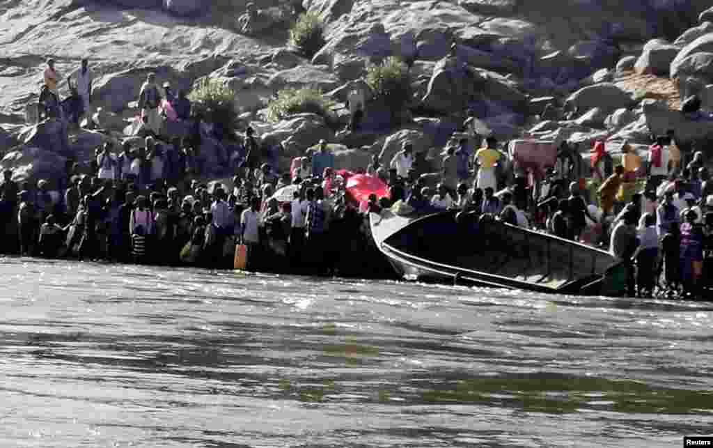 Ethiopians who fled the ongoing fighting in Tigray region prepare to cross the Setit River on the Sudan-Ethiopia border in Hamdait village in eastern Kassala state, Sudan, Nov. 14, 2020.