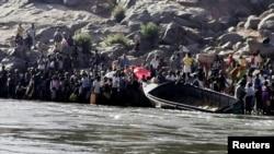 Orang-orang Etiopia yang melarikan diri dari konflik di Tigray bersiap menyeberang Sungai Setit di perbatasan Sudan-Etiopia di Desa Hamdait, di negara bagian Kassala, Sabtu, 14 November 2020.