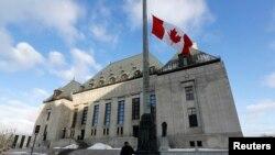 工作人員在最高法院大樓前升起加拿大國旗。(2014年3月21日)