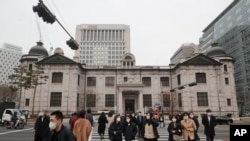 People wearing face masks walk by the headquarters of the Bank of Korea in Seoul, South Korea, March 4, 2021. South Korea's central bank says the country's economy shrank for the first time in 22 years in 2020.