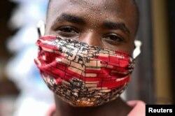 "Pierre Mahiraguha, a vendor at the Kimironko market wears a handmade ""kitenge"" cloth mask as he attempts to protect himself against the coronavirus disease (COVID-19), in Kigali, Rwanda, March 17, 2020."