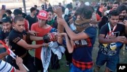 Demonstranti iznose jednog od povređenih, u Bagdadu