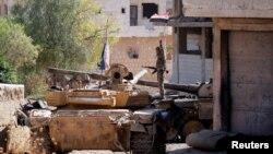 Seorang prajurit tentara Suriah memegang bendera Suriah ketika ia berdiri di atas kendaraan militer di Khan Sheikhoun, Idlib, Suriah, 24 Agustus 2019. (Foto: Reuters)