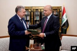 Iraqi President Barham Salih, right, instructs newly appointed Prime Minister Mohammed Allawi in Baghdad, Feb. 1, 2020.