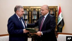 Iraqi President Barham Salih, right, instructs Prime Minister-designate Mohammed Allawi in Baghdad, Iraq, Feb. 1, 2020. Allawi was selected by rival Iraqi factions after weeks of political deadlock.